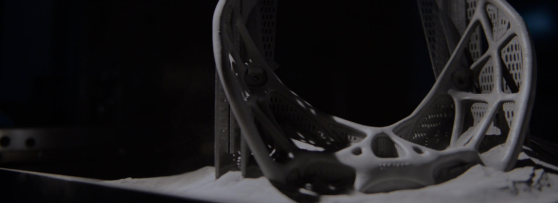 a 3D printed metal part emerging from the printer, surrounded by metal powder